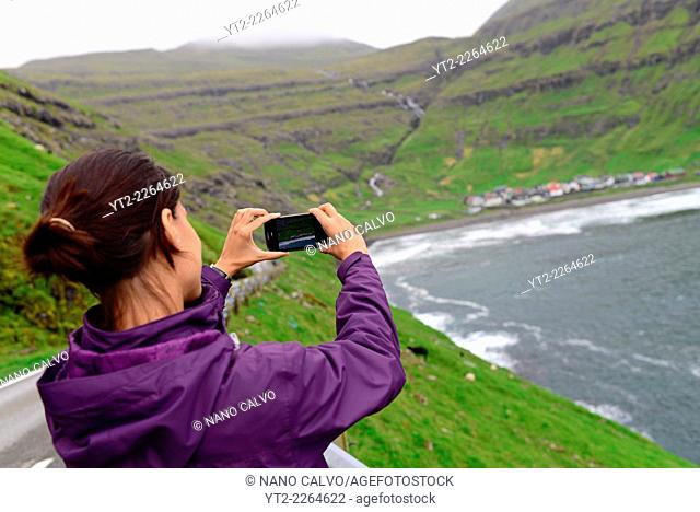 Young woman takes photo with mobile to village of Tjørnuvík, Streymoy, Faroe Islands