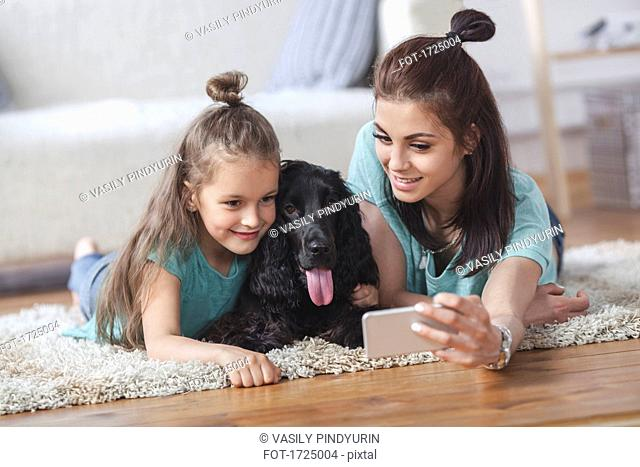 Young woman with daughter and dog taking selfie using smart phone at home