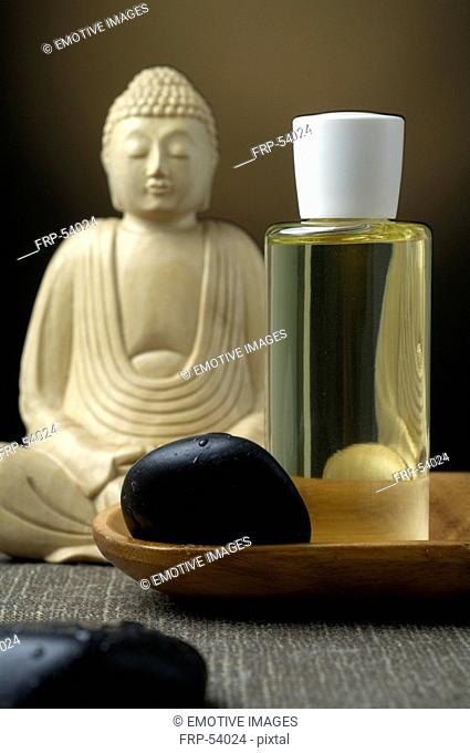 Buddha with a cosmetic bottle and black stones