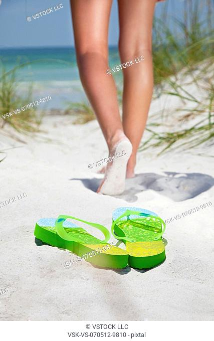 USA, Florida, St. Petersburg, Pair of flip flops on sandy beach and girl (12-13) in background