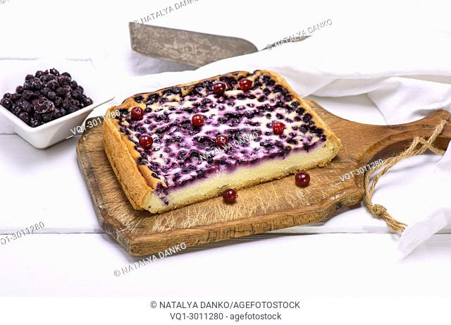 piece of pie from cottage cheese and blueberries on a brown wooden board, top view