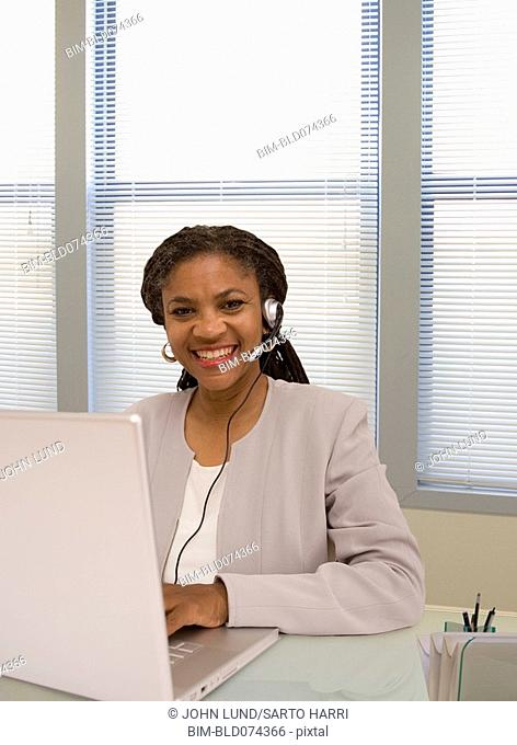 African businesswoman in headset using laptop