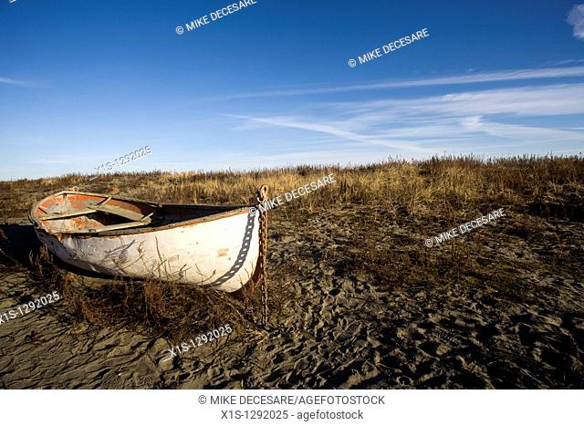 An old wooden lifeboat is beached in the sand of a nondescript location under blue skies