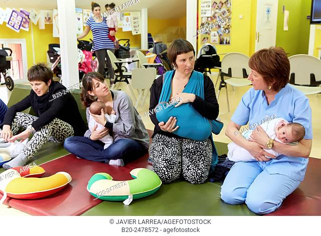 Midwife with mothers and babies at breastfeeding education program