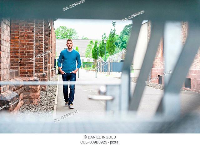 Young man walking past brick building