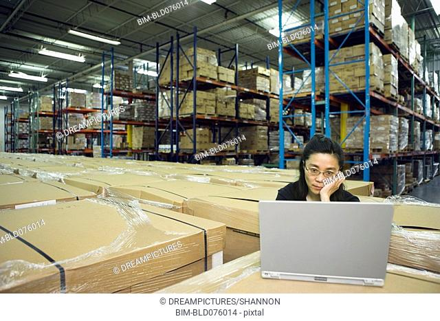 Chinese woman using laptop in warehouse