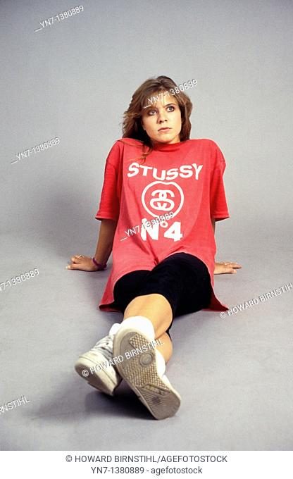 Portrait of a girl sitting on the studio floor with a slight look of contenation