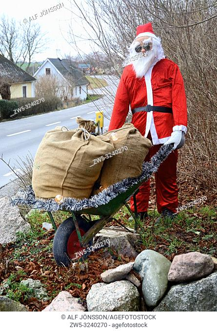 Santa Claus with a sack in a wheelbarrow in Mossby, Scania, Sweden