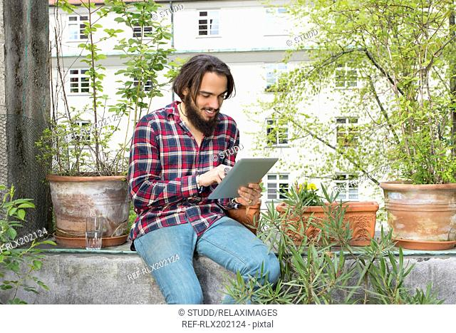 Happy young man using digital tablet in balcony