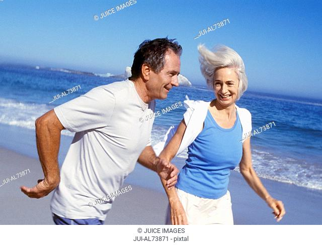 Portrait of a middle aged couple jogging on the beach