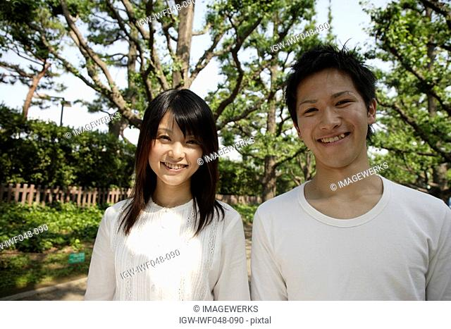 Portrait of a young couple smiling with trees in background