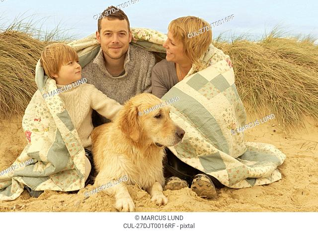 Family with dog, under quilt, on beach