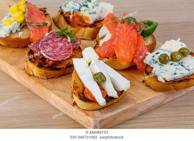 Tapas with cheese, salami, salmon, tomato and herbs