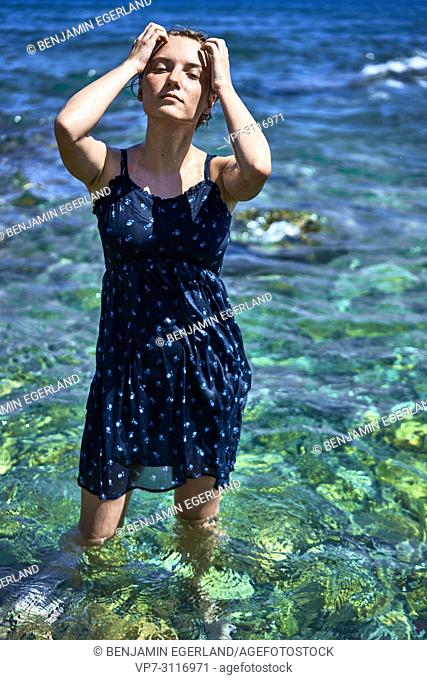 woman standing in sea water, wearing dress, sensual, in holiday destination Chersonissos, Crete, Greece