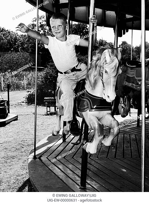 Young boy riding on merry-go-round