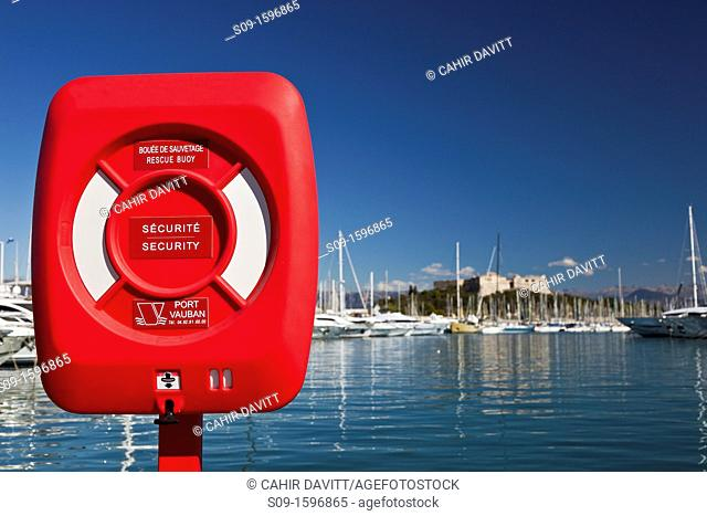Red lifebouy in the foreground with yachts in the Port Vauban Harbour and Fort Carre in the background, La Fontonne, Antibes, Provence-Alpes-Côte d'Azur, France