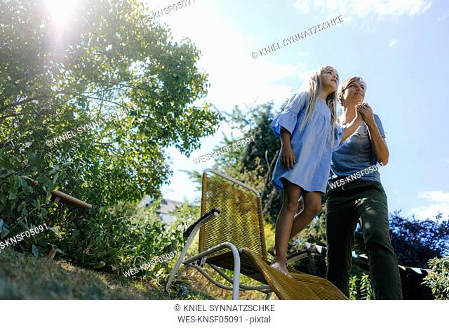 Mother and daughter in garden looking up