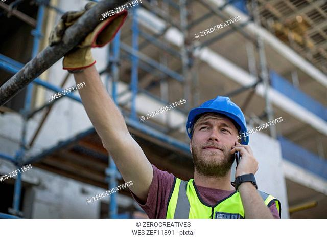 Construction worker on construction site talking on the phone
