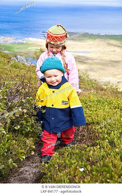 Two small girls, children, in raincoats walking along the beach, Gimsoya Island, Lofoten, Norway