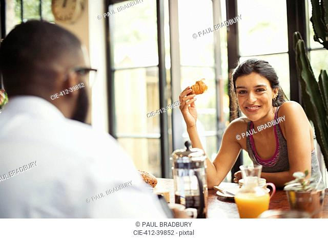 Portrait smiling young woman enjoying croissant and coffee in cafe