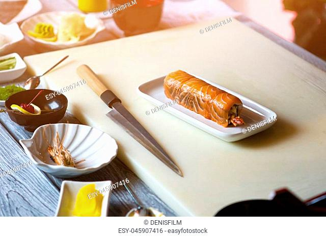 Small plate with sushi rolls. Knife lying beside sushi. Meal cooked at japanese restaurant. Dish prepared at sushi cafe