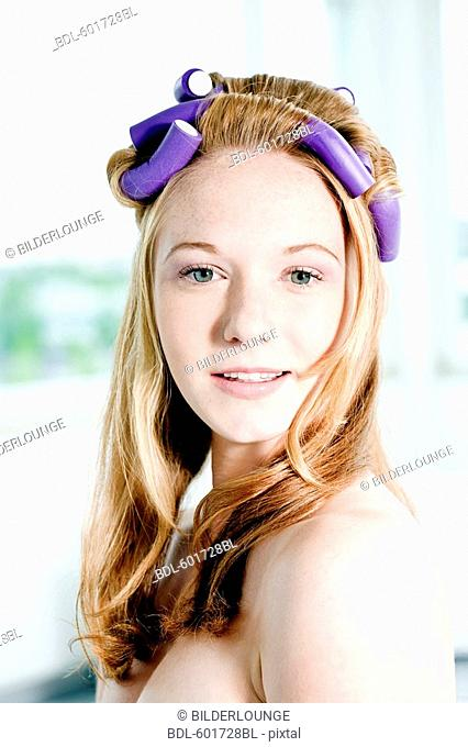 headshot of young woman with curlers in her hair