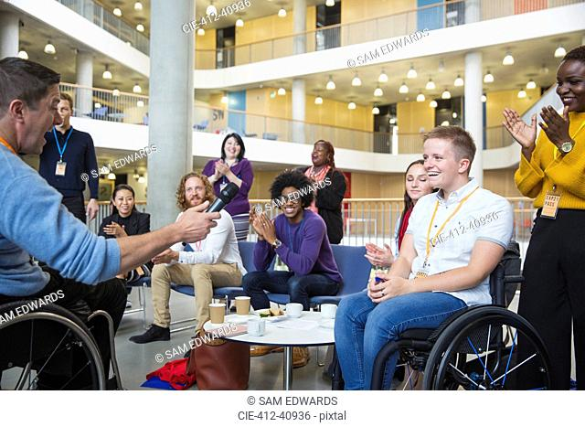 Colleagues clapping for speaker in wheelchair at conference