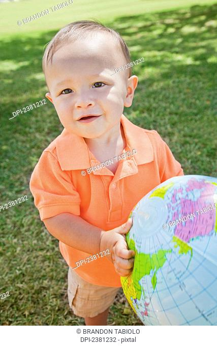 Young boy holding a globe at the park; Honolulu, Oahu, Hawaii, United States of America