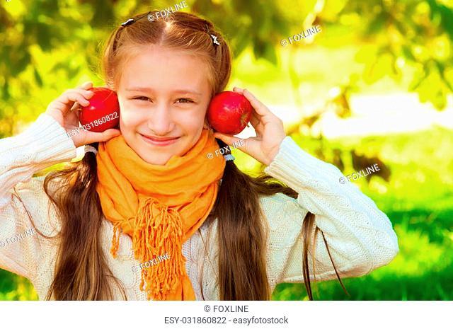 Schoolgirl with apples in autumn park