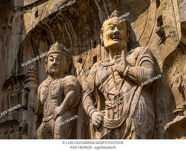 Statue of Vaisravana and warrior  North wall of Fengxiansi Cave  The grottoes were started around the year 493 when Emperor Xiaowen of the Northern Wei Dynasty...