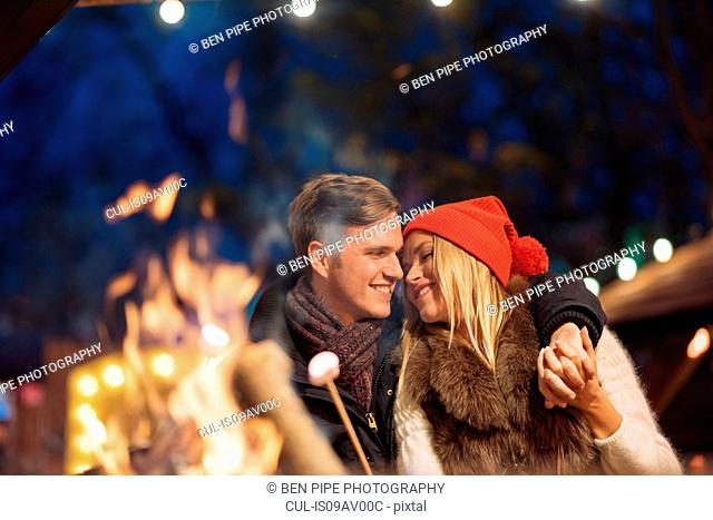 Romantic young couple toasting marshmallows at xmas festival in Hyde Park, London, UK