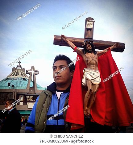 A pilgrim holds an image of Jesus Christ crucified during the annual pilgrimage to the Our Lady of Guadalupe basilica in Mexico City, Mexico