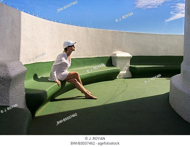 woman in white sitting in the sun