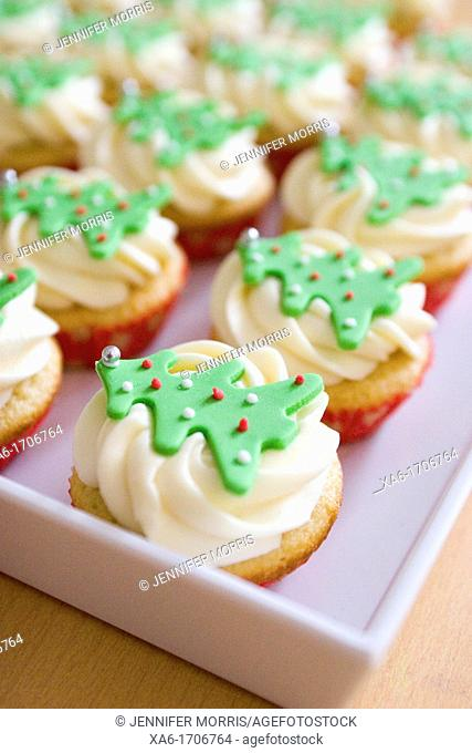 Three cupcakes with vanilla frosting swirls and Christmas tree decorations on