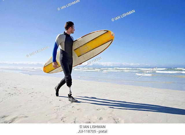 Surfer With Artificial Leg Standing On Beach