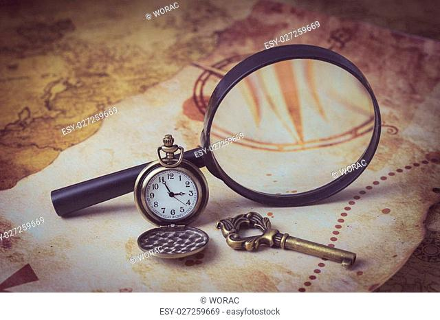 Old map with magnifying glass, pocket watch and old key