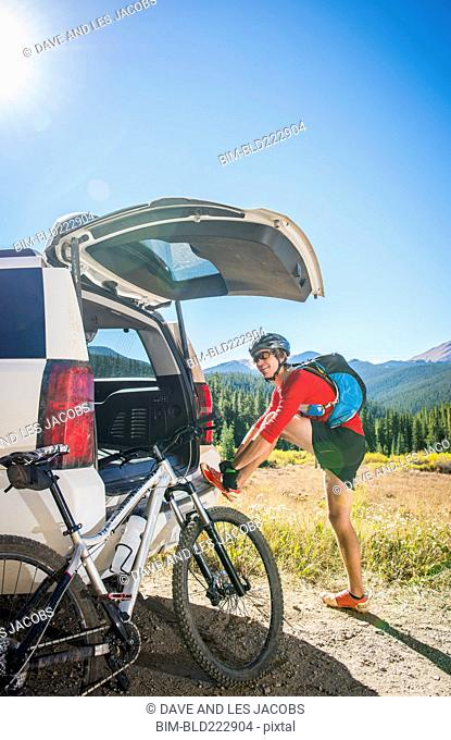 Caucasian man with mountain bike fastening shoe at car hatch