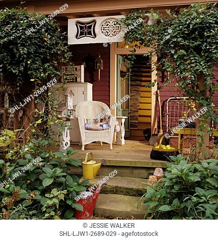 PORCH: Country porch, open door, wicker chair, watering cans on concrete steps, folk art and architectural salvage decorate, climbing vines, autumn season