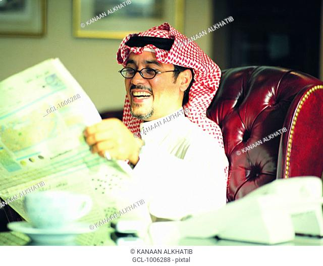 Saudi businessman laughing while reading newspaper