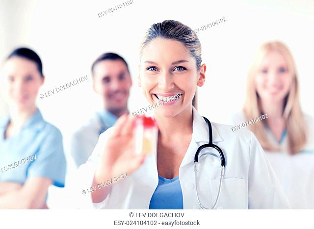 healthcare and medical concept - young female doctor with jar of capsules