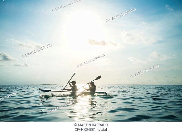 Women in clear bottom canoe on sunny, idyllic ocean, Maldives, Indian Ocean