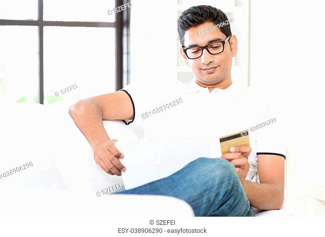 Indian guy hand holding credit card, enjoying internet online shopping using digital computer tablet at home. Asian man relaxed and sitting on sofa indoor