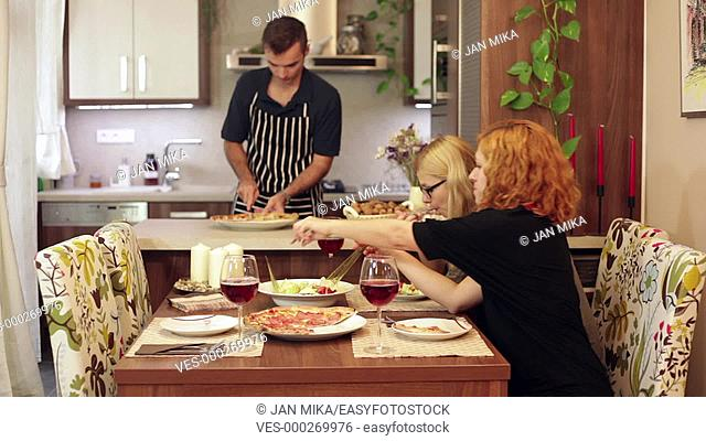 A man preparing lunch while two women sitting and eating behind the table at home