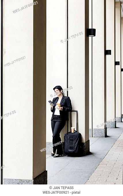 Businesswoman with trolley using smart phone, while eating croissant