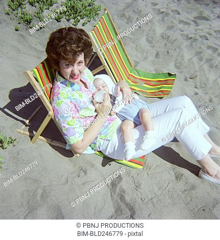 Caucasian mother sitting on beach feeding bottle to baby son