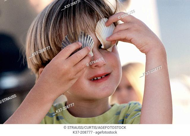 Young boy holding shells over his eyes