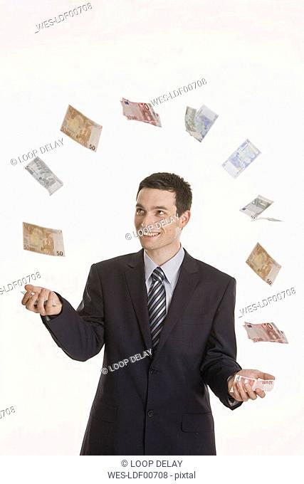 Businessman juggling Euro notes