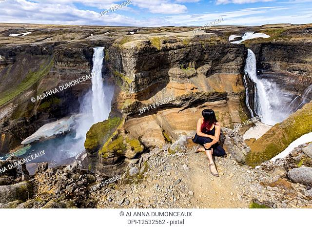 A young asian female hiker poses for a portrait on the edge of a stunning double waterfall valley landscape known as Haifoss; Iceland