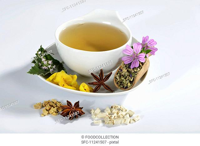 A cup of herbal tea with marsh mallow leaves, marsh mallow root, liquorice, thyme, lungwort, star anise, mallow flowers and mullein flowers