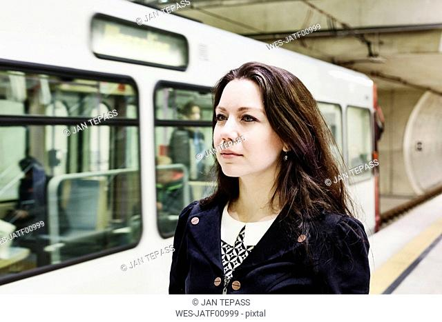 Germany, Cologne, portrait of young woman waiting at underground station platform